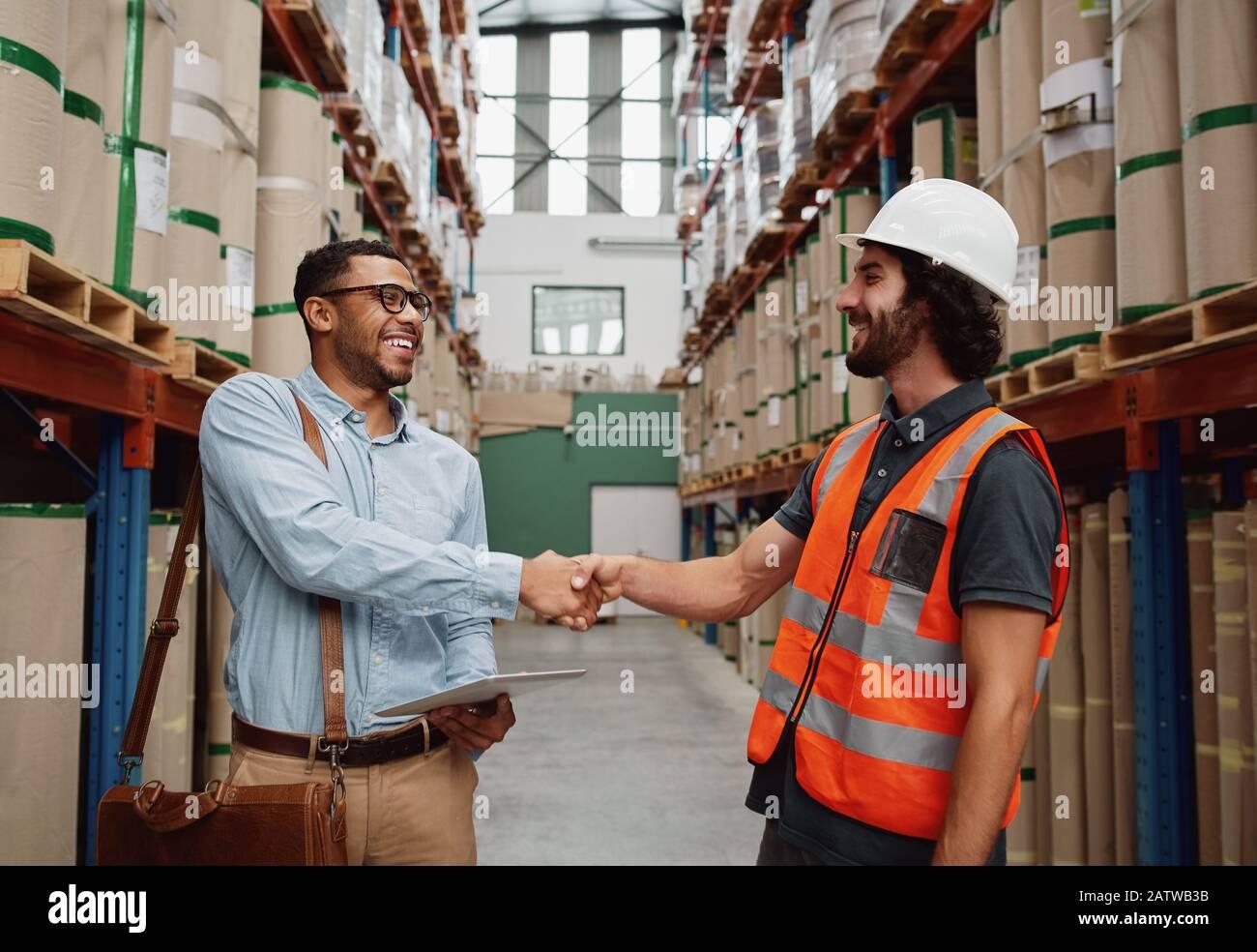 Heureux partenaire d'affaires saluant travailleur d'entrepôt dans une usine à grande échelle - banquier accorde au travailleur d'usine son prêt Banque D'Images