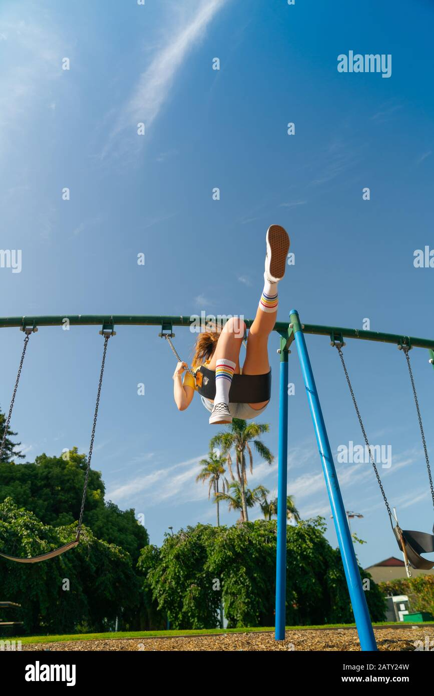 Une adolescente balançant haut dans les équipements de terrain de jeux pour enfants au domaine de Tauranga, en Nouvelle-Zélande. Banque D'Images