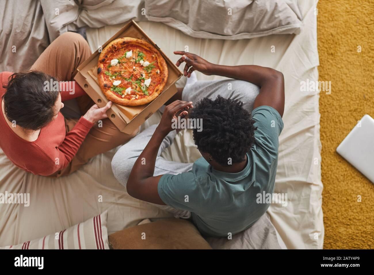 Vue sur le grand angle des jeunes couples assis sur le lit et manger de la pizza ensemble dans la chambre Banque D'Images