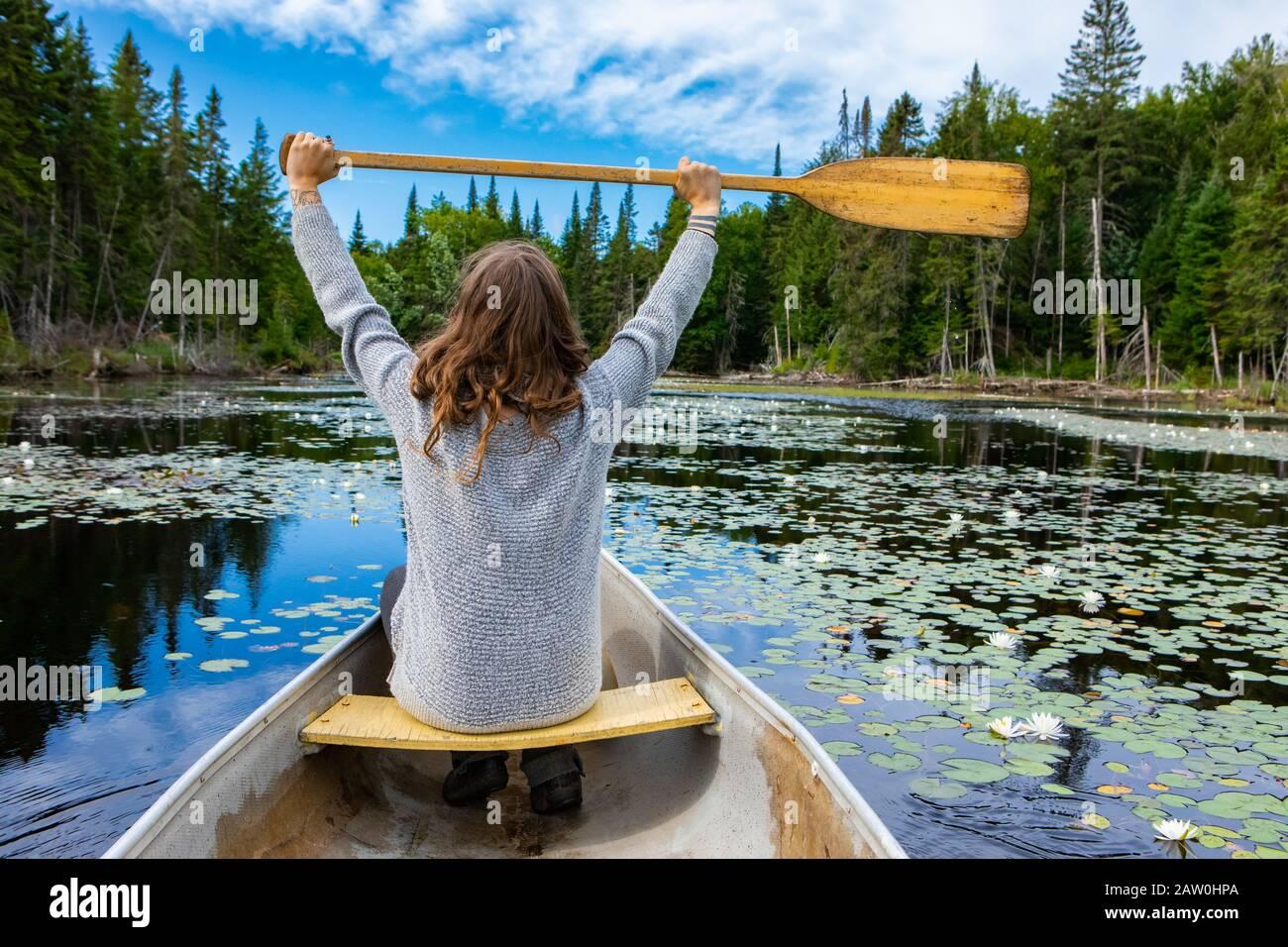 Vue arrière des jeunes touristes se sont élevés en paddle haut tout en étant assis en canoë dans le lac avec des nénuphars. Pendant le voyage dans le nord du Québec au Canada Banque D'Images