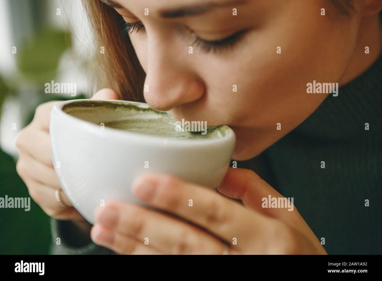 Close-up face ou portrait d'une fille qui boit sain et délicieux thé vert matcha latte Banque D'Images