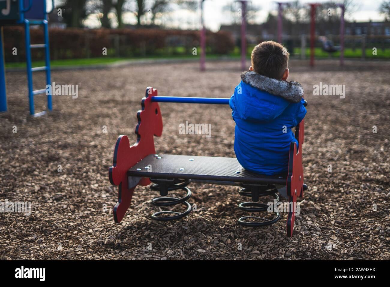 le dos d'un petit garçon jouant seul dans un stationnement Banque D'Images