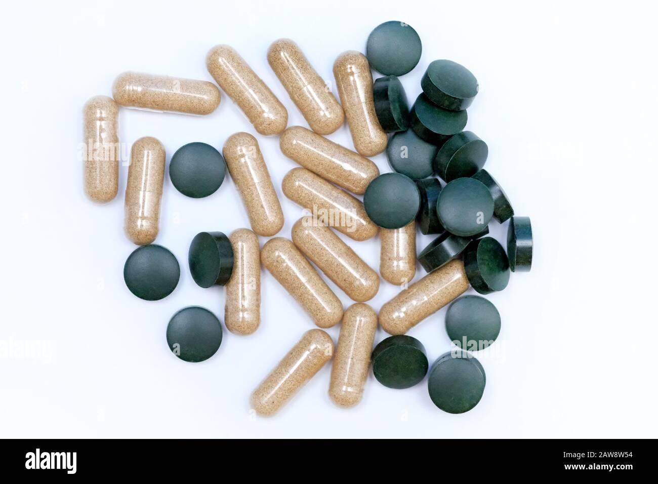 Pilules et capsules rondes vertes vue de dessus. Compléments alimentaires en comprimés. Capsules d'aloès et de chlorella en comprimés sur fond blanc. L'utilisation d'algues Banque D'Images