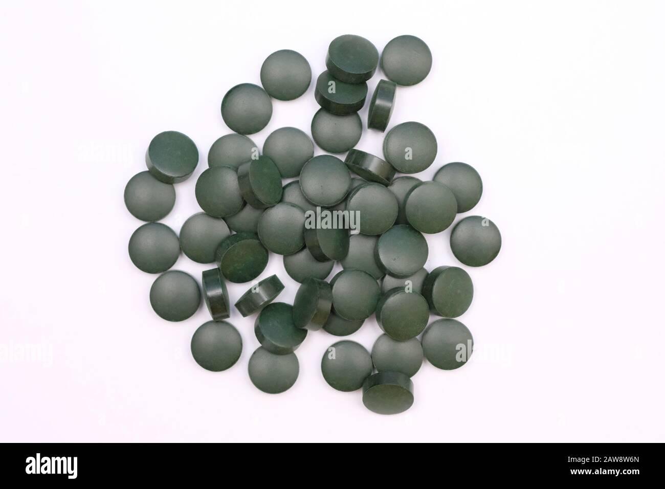 Pilules rondes vertes vue de dessus sur un fond blanc. Comprimés de spiruline, suppléments alimentaires utiles. Banque D'Images