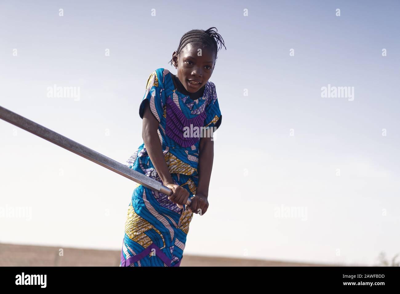 Joyeuse ethnicité africaine jeune femme Transportant de l'eau pure à Bamako Banque D'Images
