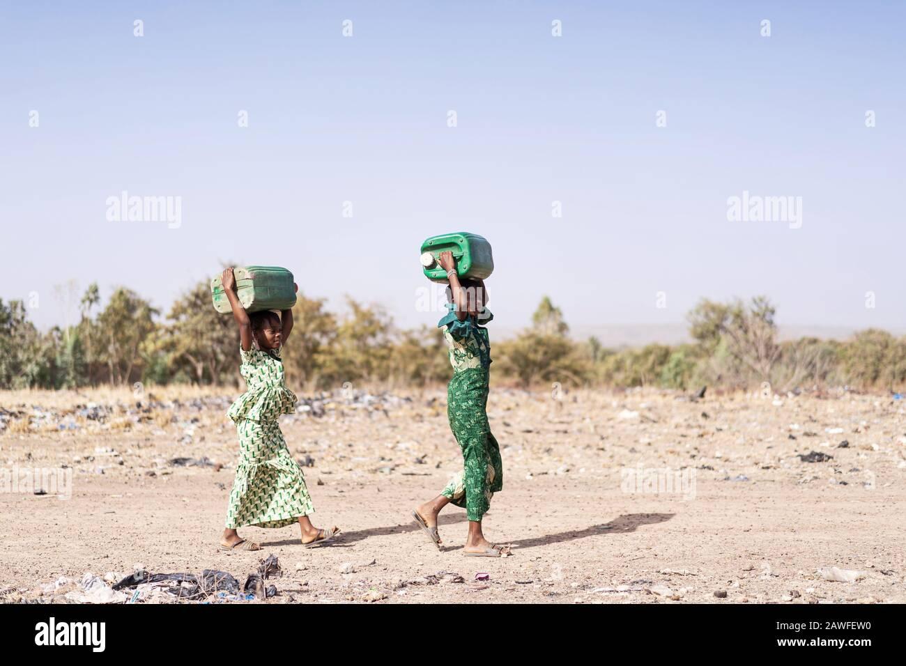 Joyeuse ethnicité africaine Juvenile Rassemblement de l'eau propre dans un village typique Banque D'Images