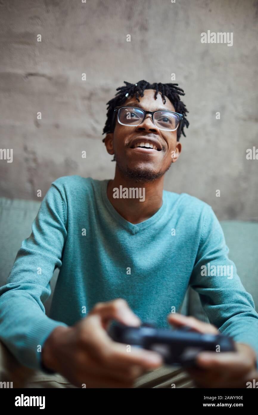 Portrait à faible angle de l'homme afro-américain souriant jouant aux jeux vidéo via une console de jeu Banque D'Images