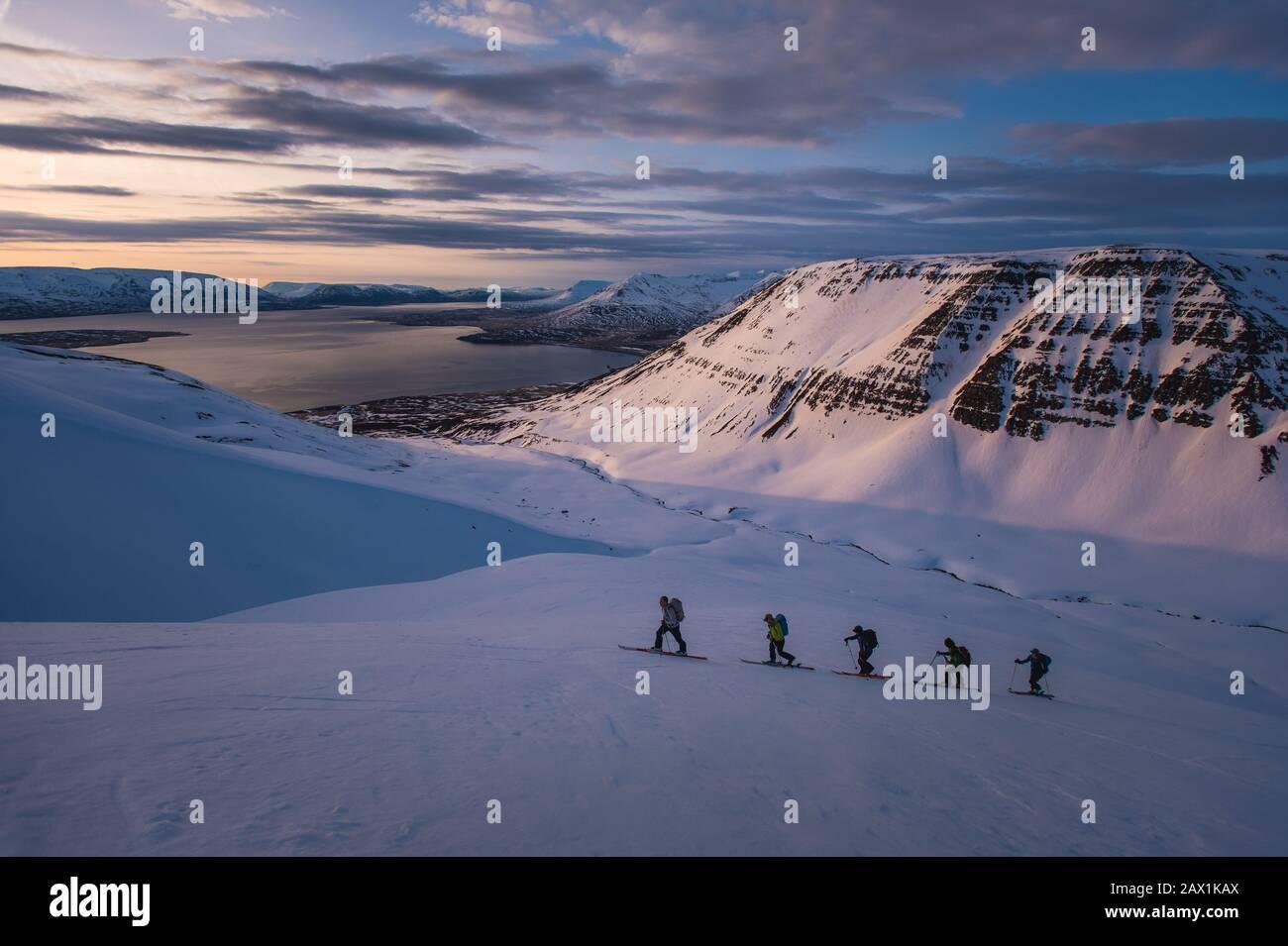 Groupe de personnes ski de fond au lever du soleil en Islande Banque D'Images
