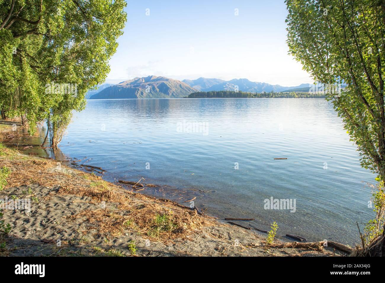 Lever du soleil du lac tôt le matin avec lumière dorée. Ciel bleu et eau. Lac Wanaka Nouvelle-Zélande, destination De voyage Populaire. Banque D'Images