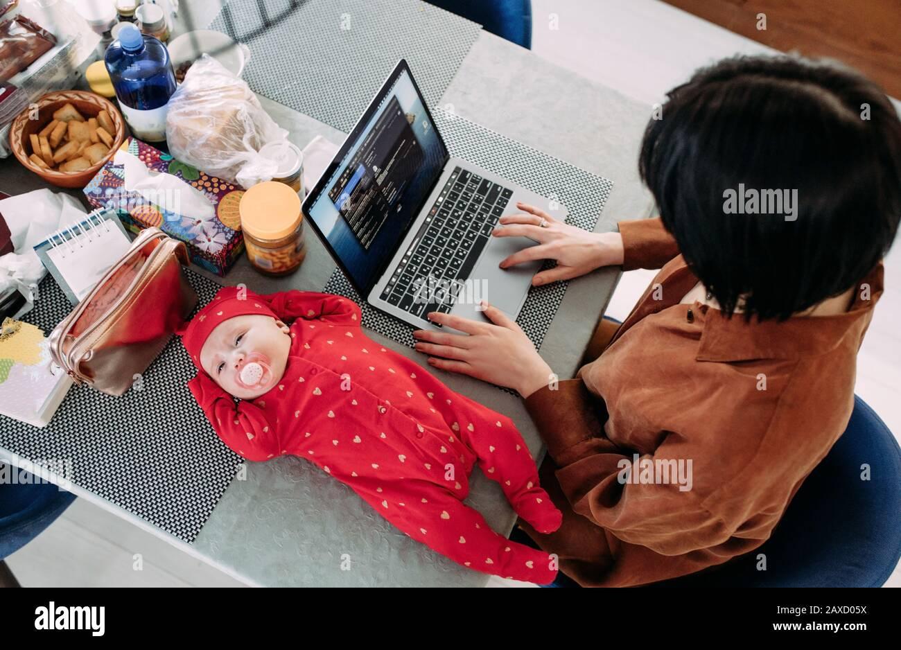La mère est assise et travaille sur un ordinateur portable près du bébé allongé sur la table. Concept d'emploi des femmes avec des bébés. Vue de dessus. Banque D'Images