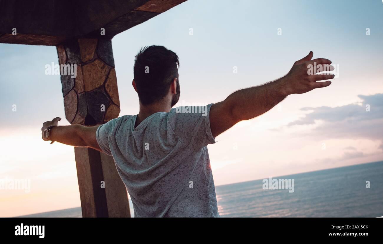 Homme qui ouvre ses bras à la vue sur la mer et trouve la paix. Concept De Liberté. Banque D'Images