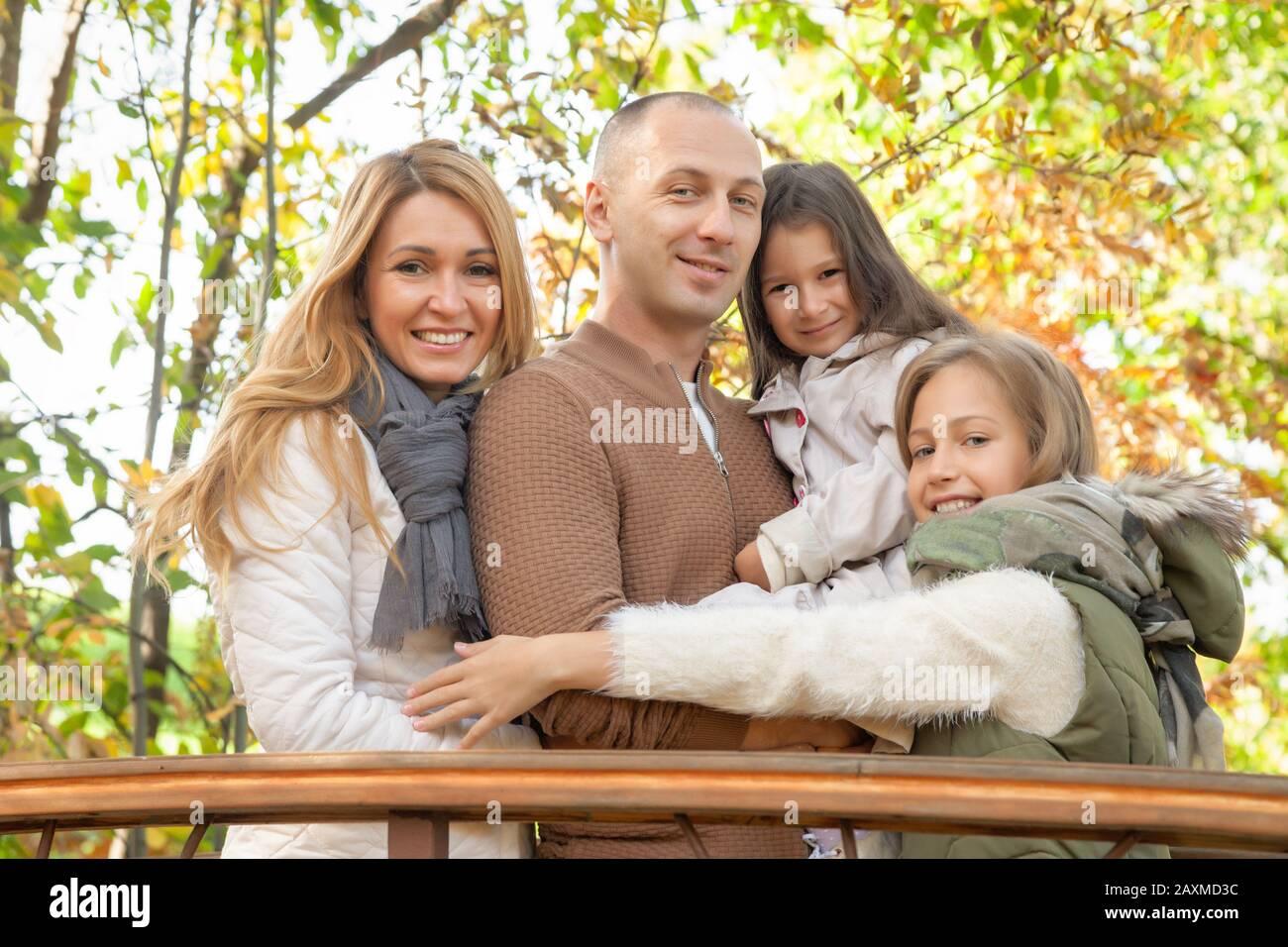 Famille heureuse, femme, mari, filles, marcher avec les enfants sur le pont, jouer dans le parc d'automne, s'amuser dans la forêt, se détendre à l'extérieur. Amusant, enfant Banque D'Images
