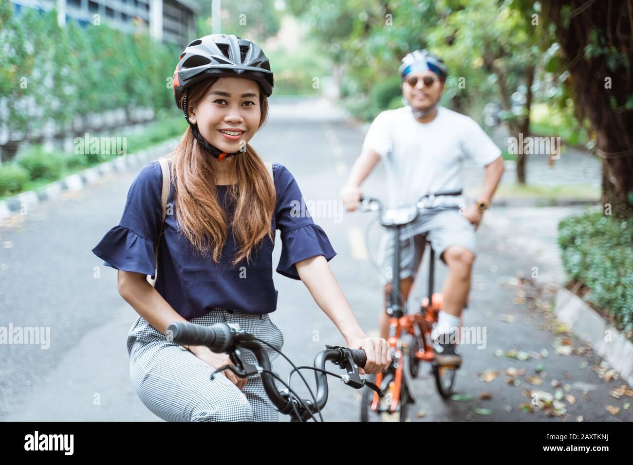 les jeunes couples asiatiques qui portent un casque apprécient de faire du vélo d'équitation ensemble lors de leurs excursions dans le parc Banque D'Images