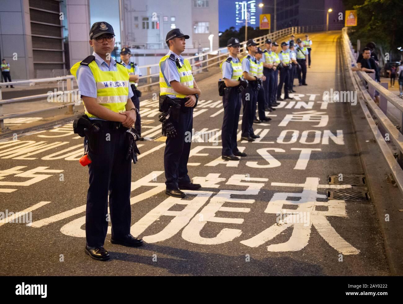 Hong Kong, Chine : 16 Juin 2019. Policier repose sa main sur une bombe de poivre, prêt si un manifestant sort de la ligne.Les Manifestants marchent à travers Wan Banque D'Images
