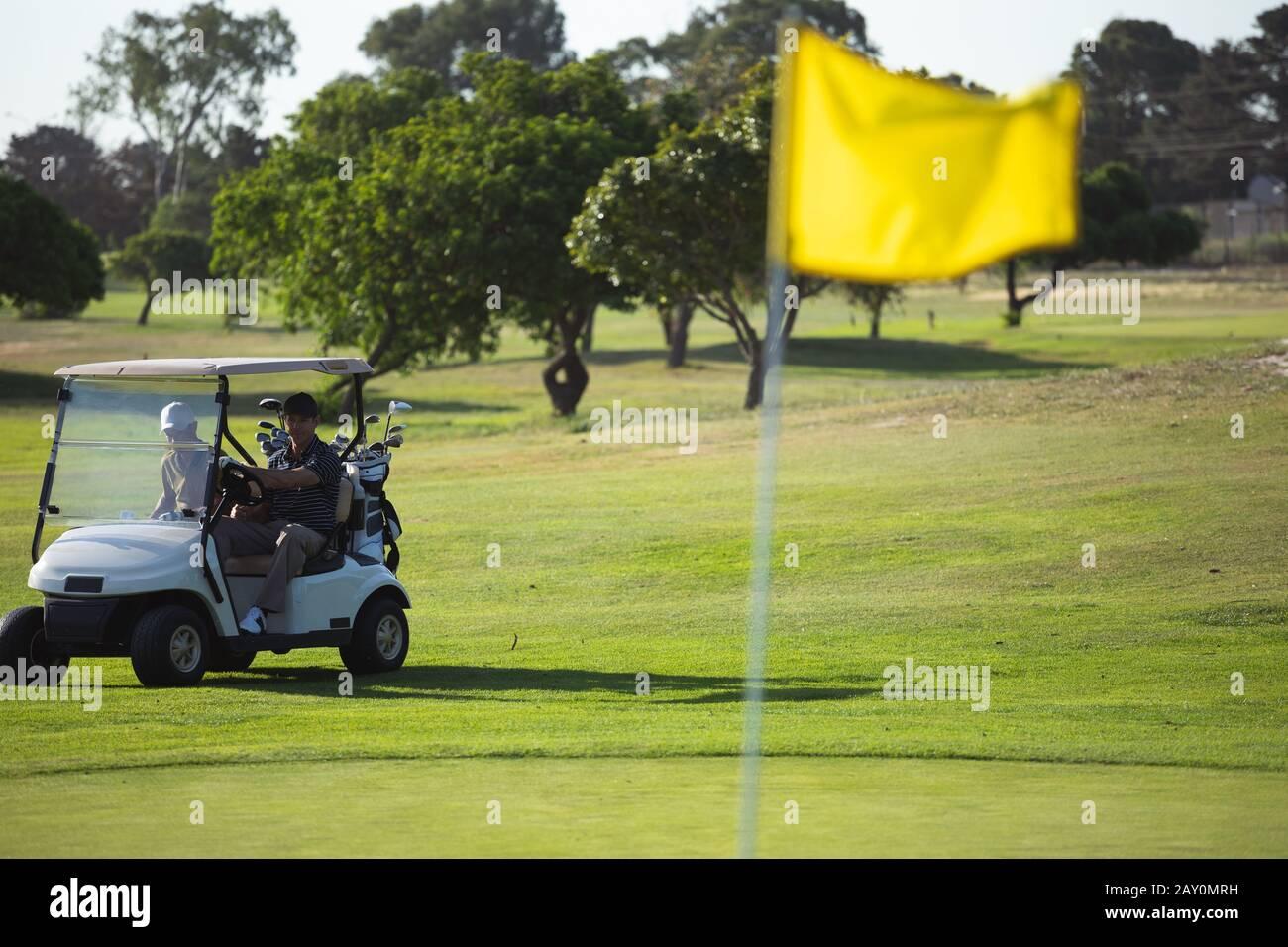 Les golfeurs qui conduisent le buggy de golf Banque D'Images