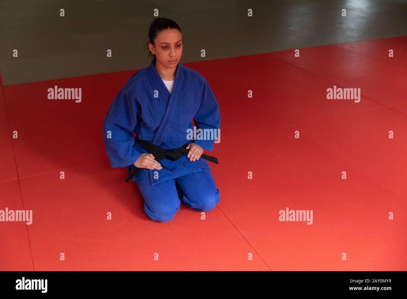 Judoka s'agenouillant sur des tapis dans la salle de gym avant de s'entraîner à judo Banque D'Images