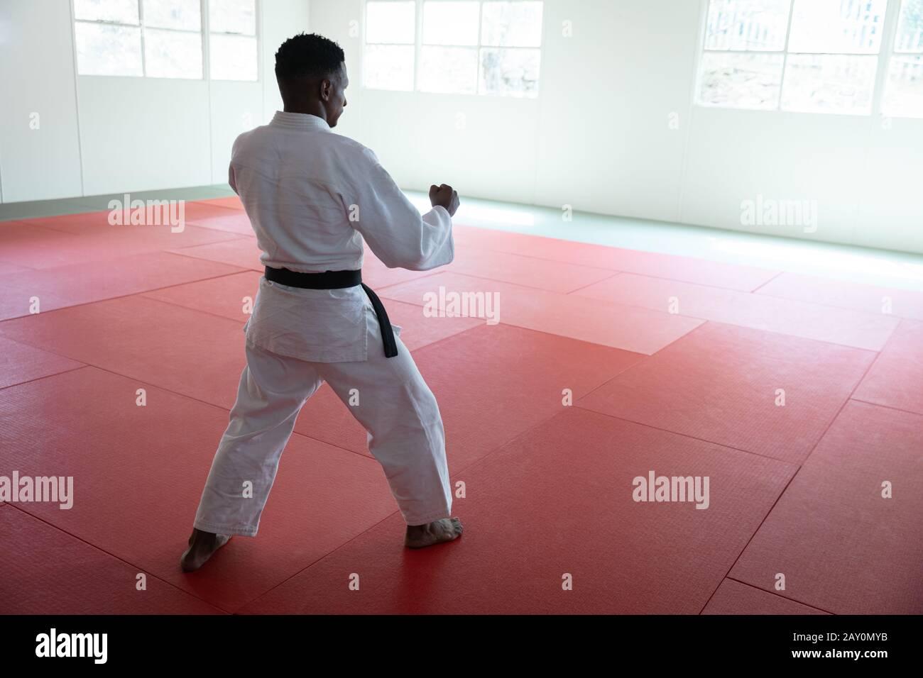karateka frappant une pose dans une salle de sport Banque D'Images