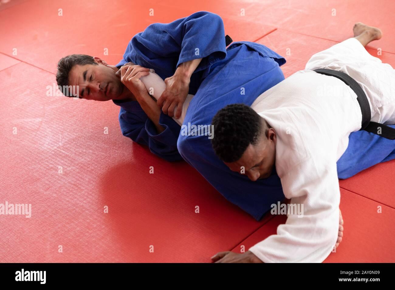 Judokas pratiquant le judo pendant un sparing dans une salle de sport Banque D'Images