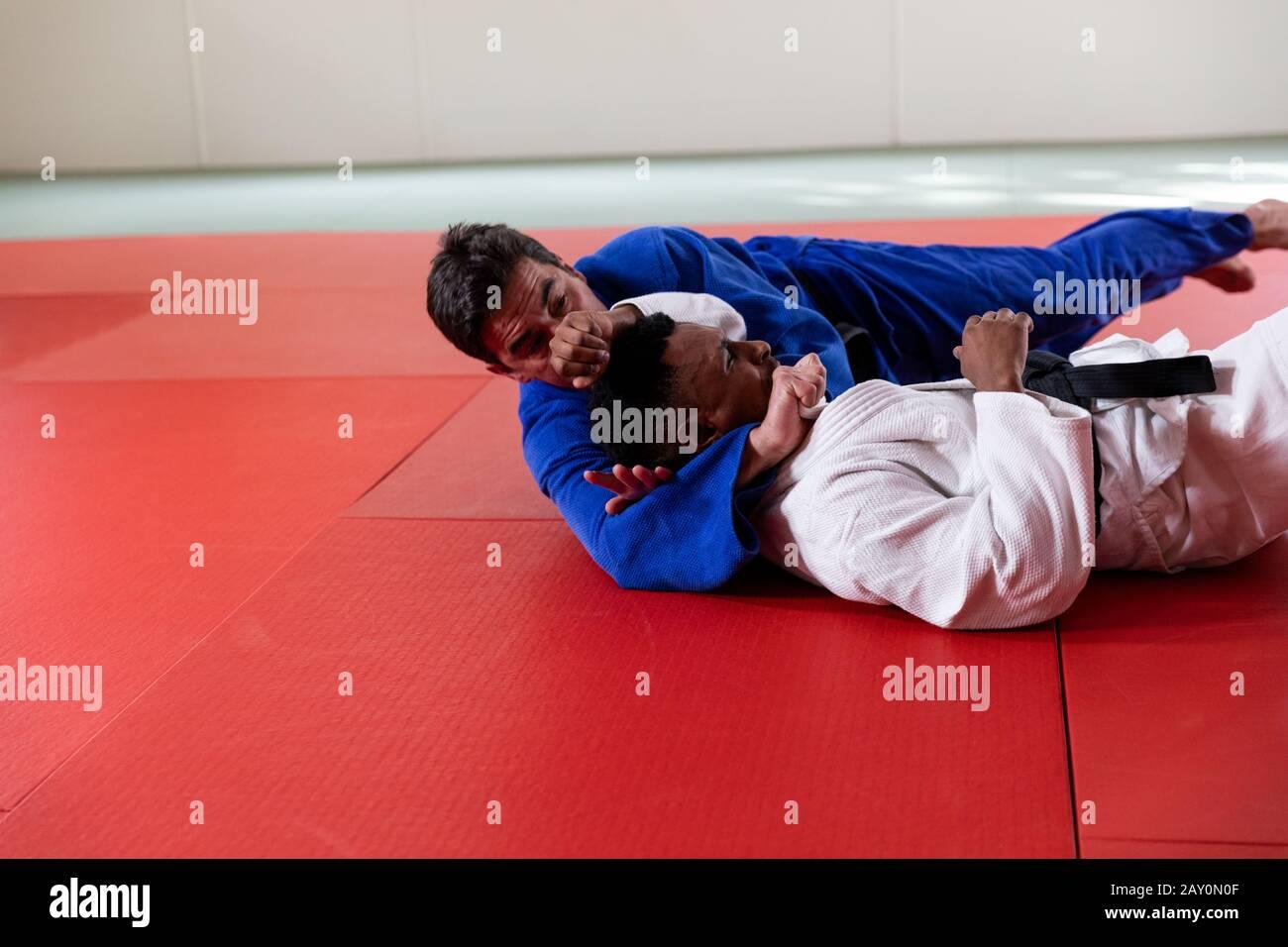 Judokas pratiquant le judo pendant un entraînement dans une salle de sport Banque D'Images