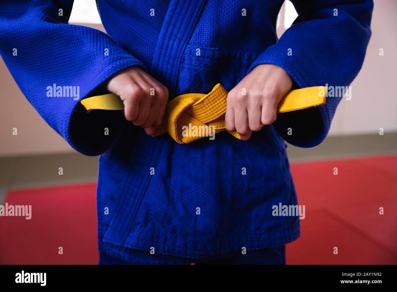 Judoka mettant sur la ceinture jaune Banque D'Images