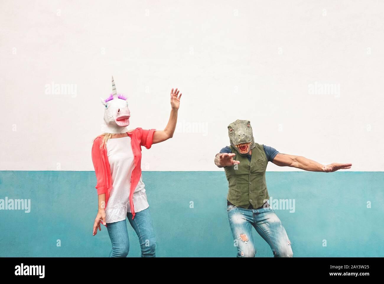 Joyeux couple fou dansant tout en portant le t-rex et le masque unicorn en plein air - les aînés s'amusent à célébrer le festival du carnaval Banque D'Images