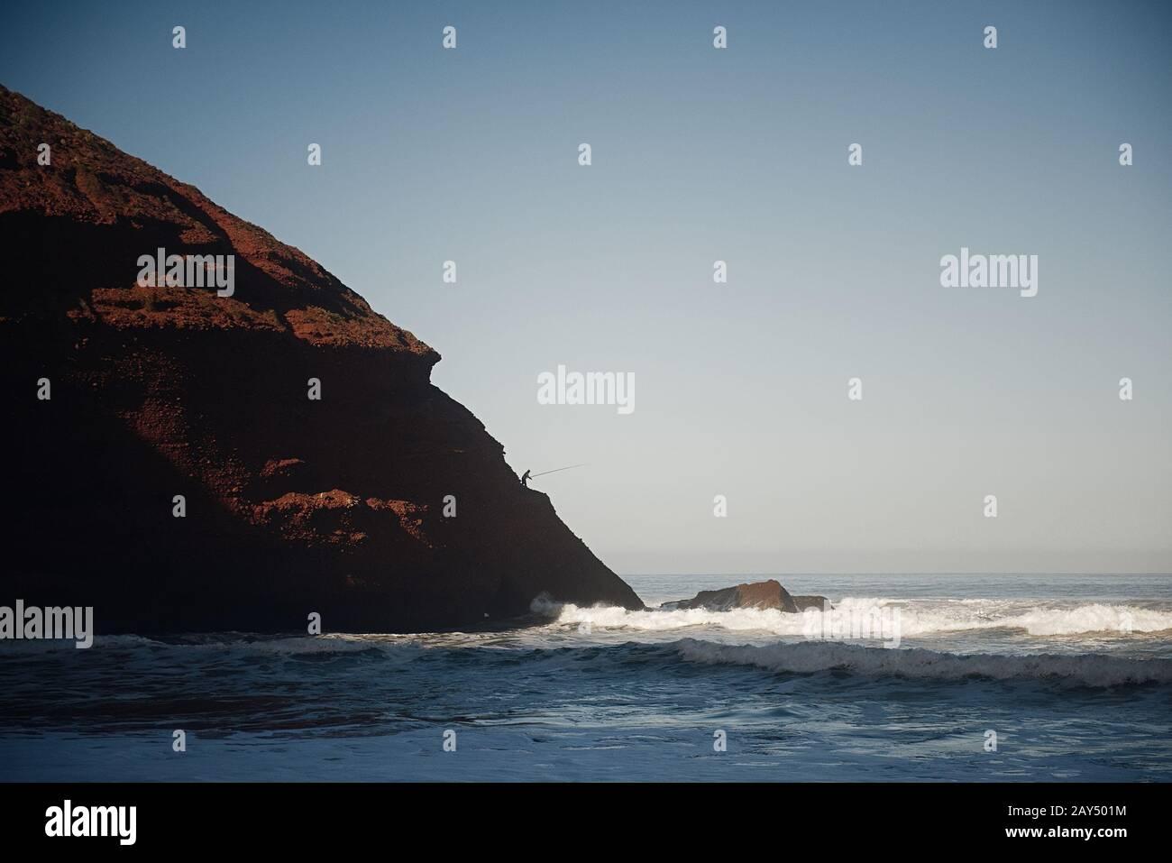 Legzira des voûtes en pierre naturelle spectaculaires qui s'atteignent au-dessus de la mer, de l'océan Atlantique, du Maroc, de l'Afrique. Pêcheur sur le bord. Banque D'Images