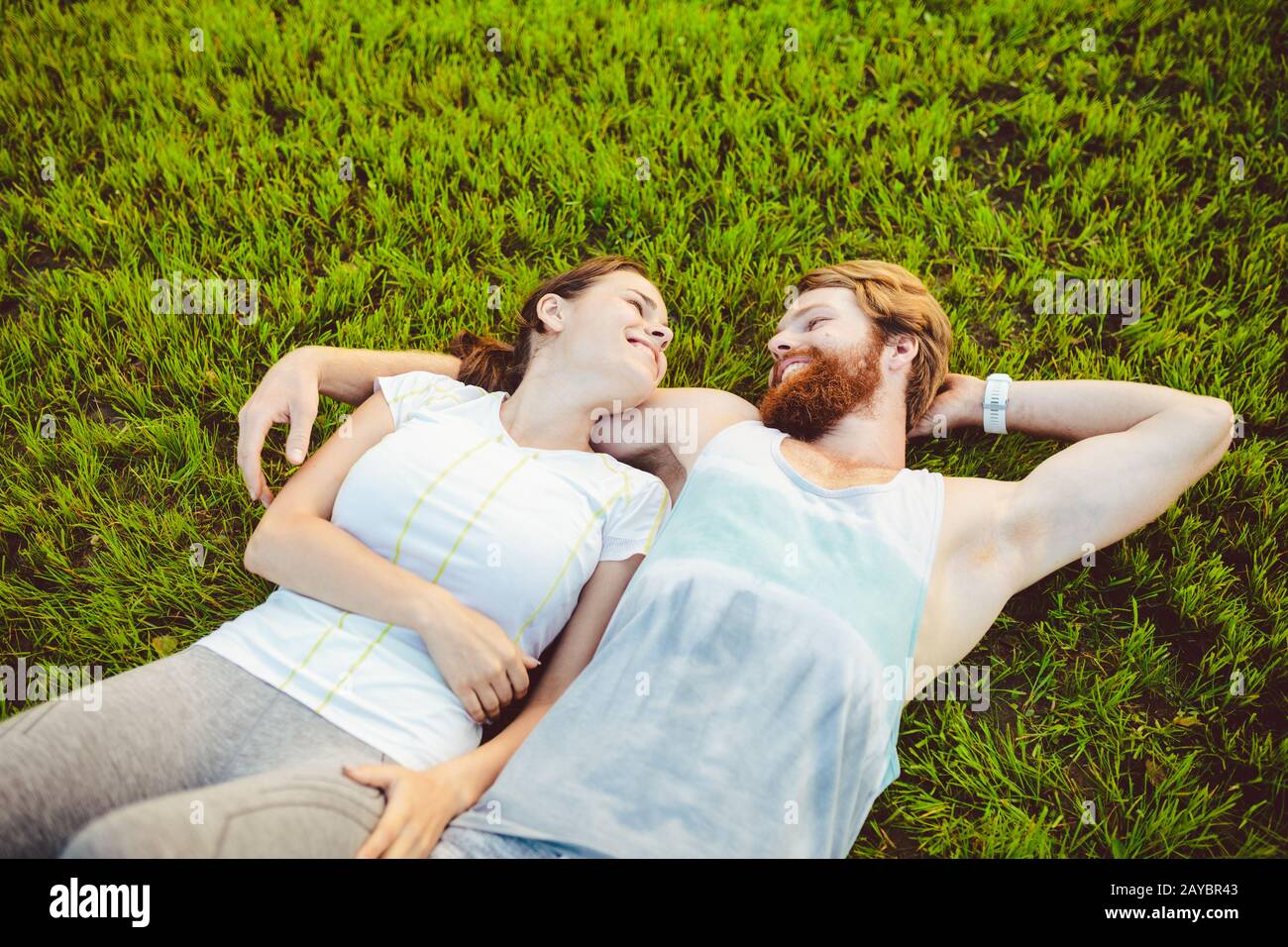 Le thème est le sport et un style de vie sain. Un jeune homme et un couple de femmes reposent sur leur dos sur l'herbe verte, une pelouse Banque D'Images