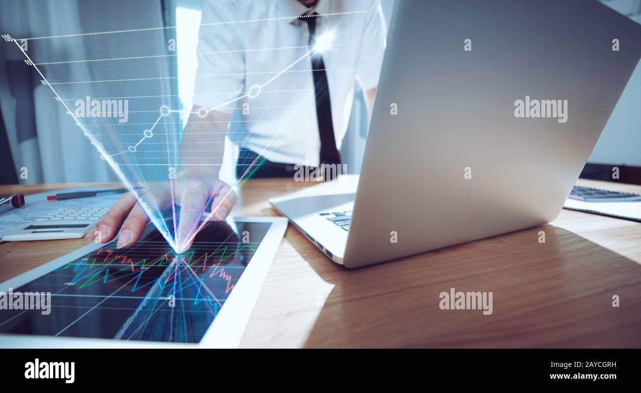 Homme d'affaires utilisant un ordinateur portable et une tablette numérique pour analyser le rapport de vente Banque D'Images