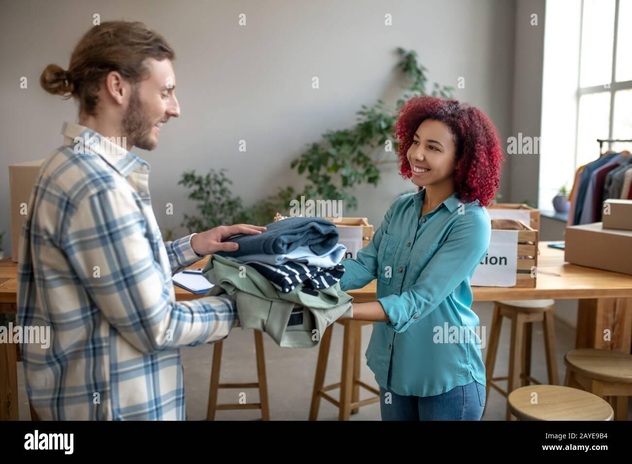 Jeune fille et homme emballage des vêtements pour aider ceux dans le besoin. Banque D'Images