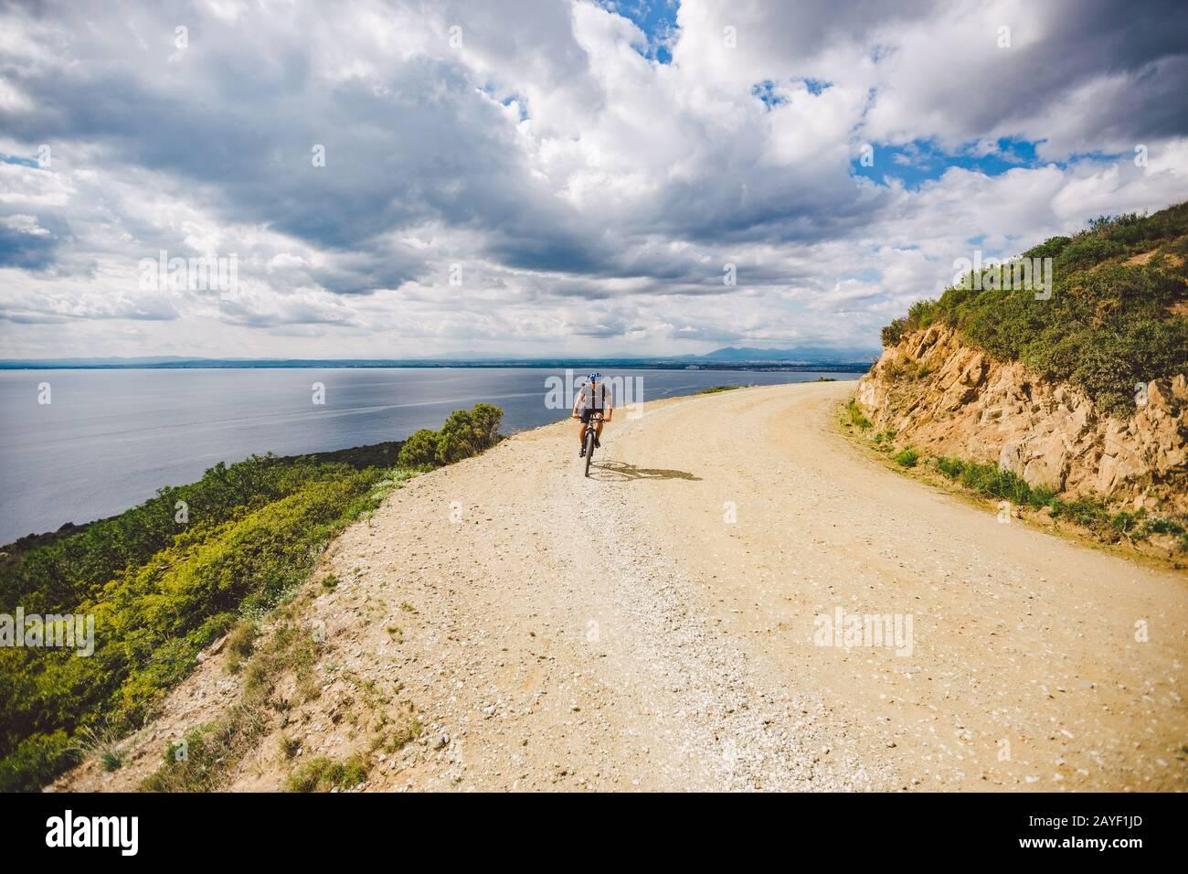 Jeune gars à vélo de montagne sur un parcours de vélo en Espagne. Athlète sur un vélo de montagne se déplace hors de la route sur le fond o Banque D'Images