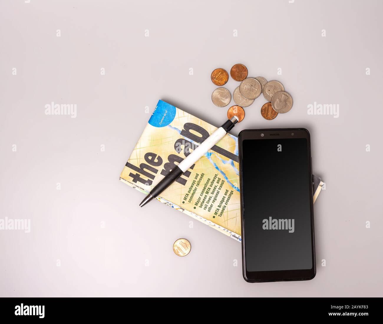 Téléphone, argent, stylo et carte pliée sur fond gris. Vue de dessus. Gros plan. Banque D'Images