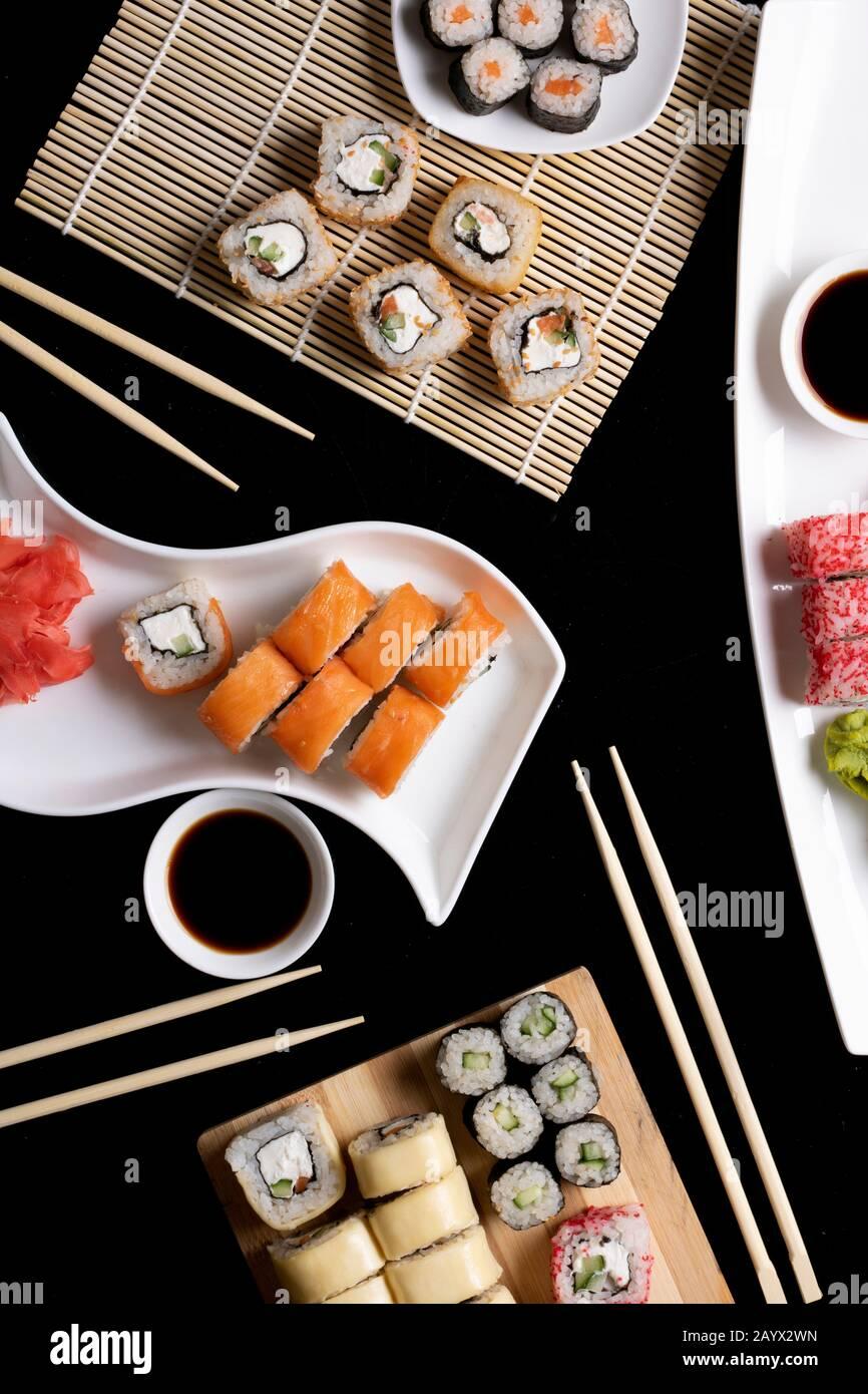 Sushi avec baguettes. Les sushis roulent la cuisine japonaise au restaurant. Jeu de rouleaux de sushi de Californie avec saumon, légumes. Image verticale Banque D'Images