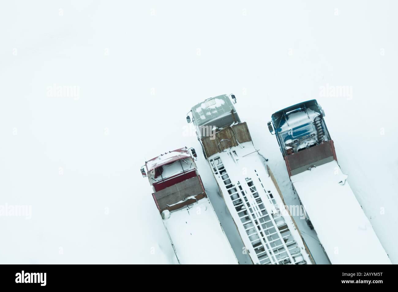 Camion sous la neige. Camion recouvert de neige après la neige. Camions longs se tiennent dans une vue de dessus de rangée. Concept de transport. Véhicules enneigés. AERI Banque D'Images