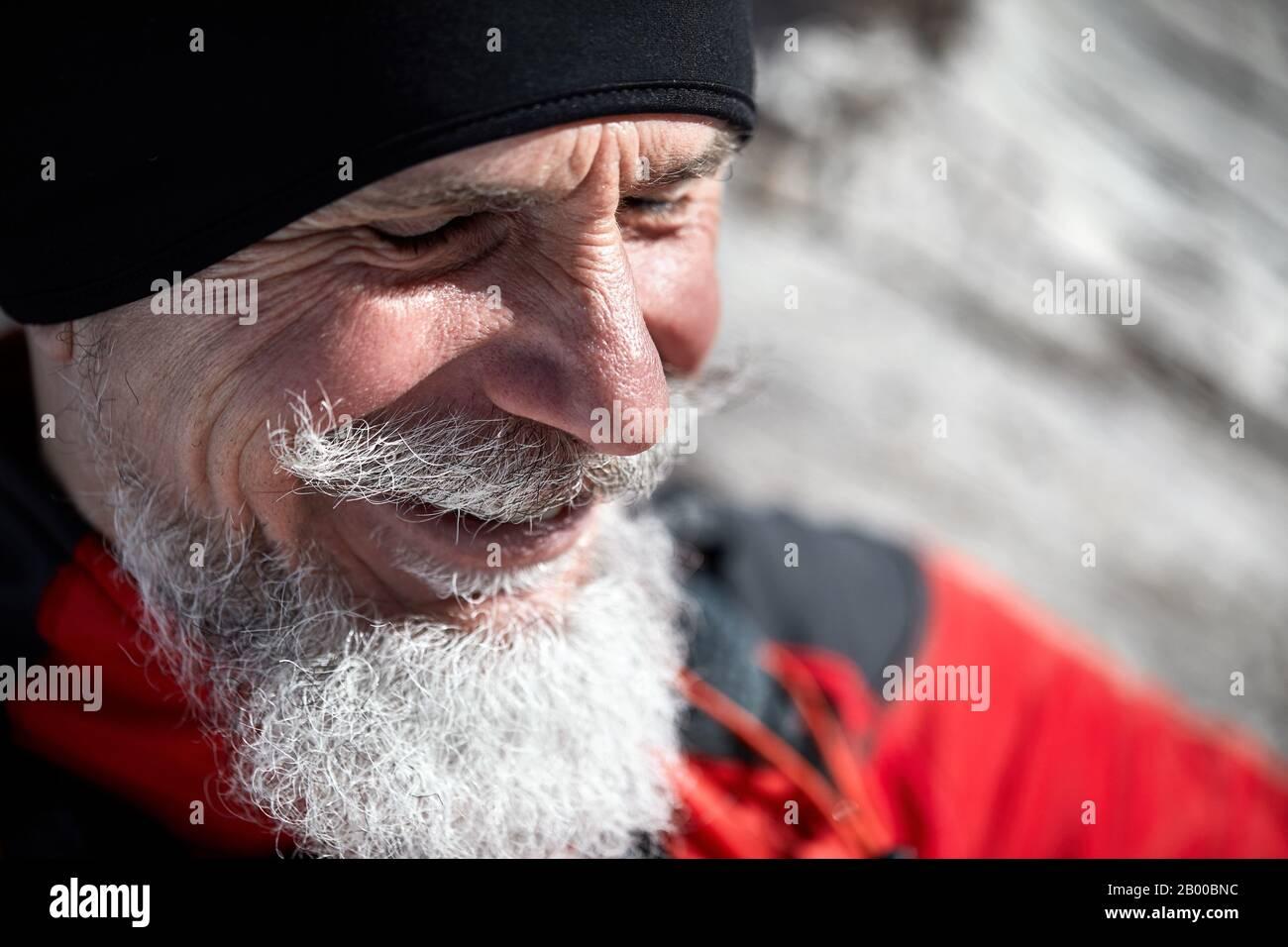 Portrait d'un homme de coureur âgé avec barbe grise souriant sur fond de montagne d'hiver Banque D'Images