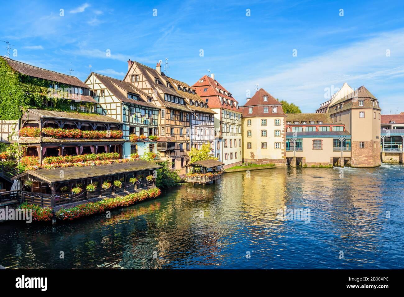 Bâtiments à colombages et anciens moulins à eau bordant la rivière Malade dans le quartier de la petite France à Strasbourg, en France, un matin ensoleillé. Banque D'Images