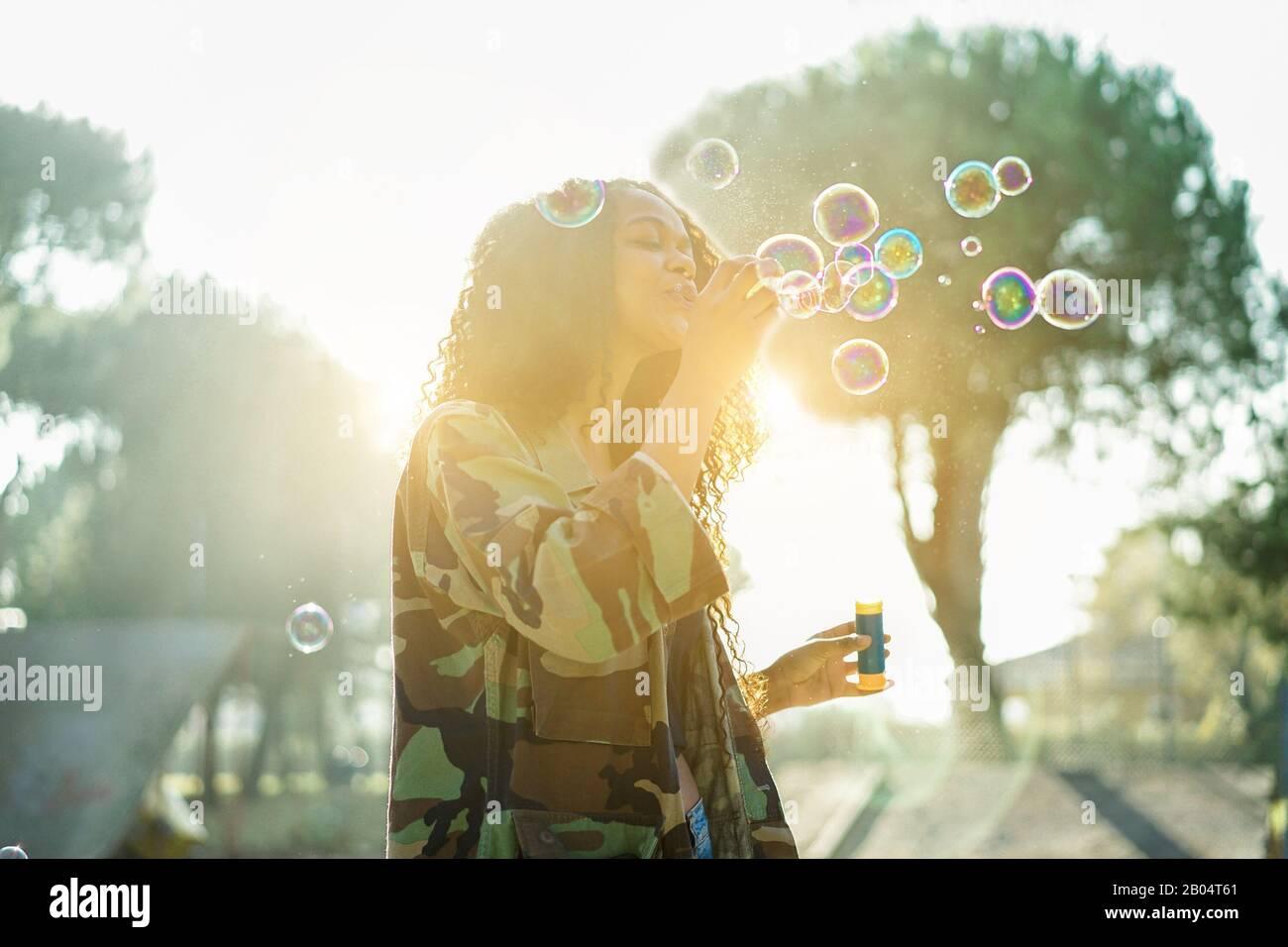 Jeune afro cheveux femme soufflant bulle de savon dans le parc de skate de ville avec le soleil arrière lumière - Portrait de fille africaine heureuse ayant plaisir en plein air - bonheur conce Banque D'Images