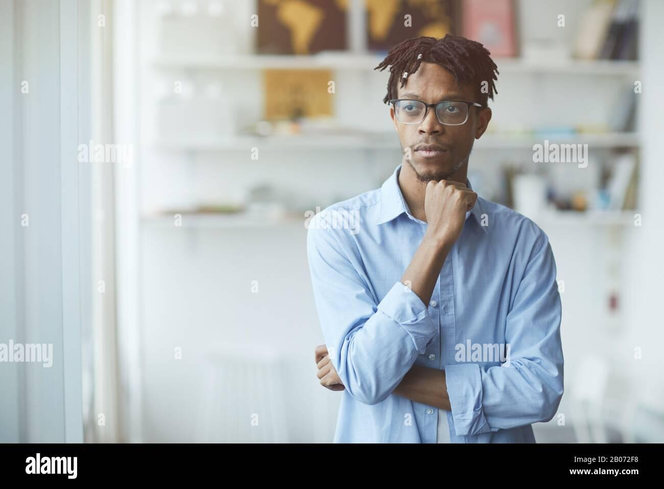 Homme d'affaires africain pensif dans les lunettes se tenant au bureau et regardant il pense à quelque chose Banque D'Images