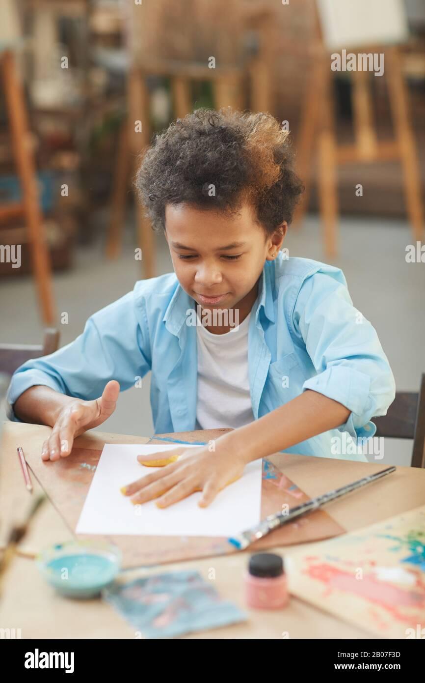 Petit garçon africain assis à la table et faire un artisanal avec des peintures au studio d'art Banque D'Images