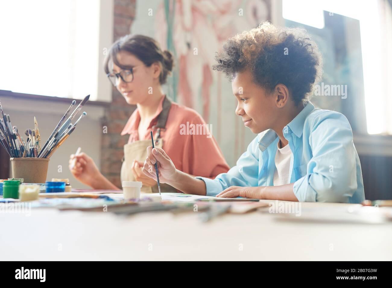 Jeune femme assise à la table avec un garçon africain et ils peignent avec des aquarelles au studio d'art Banque D'Images