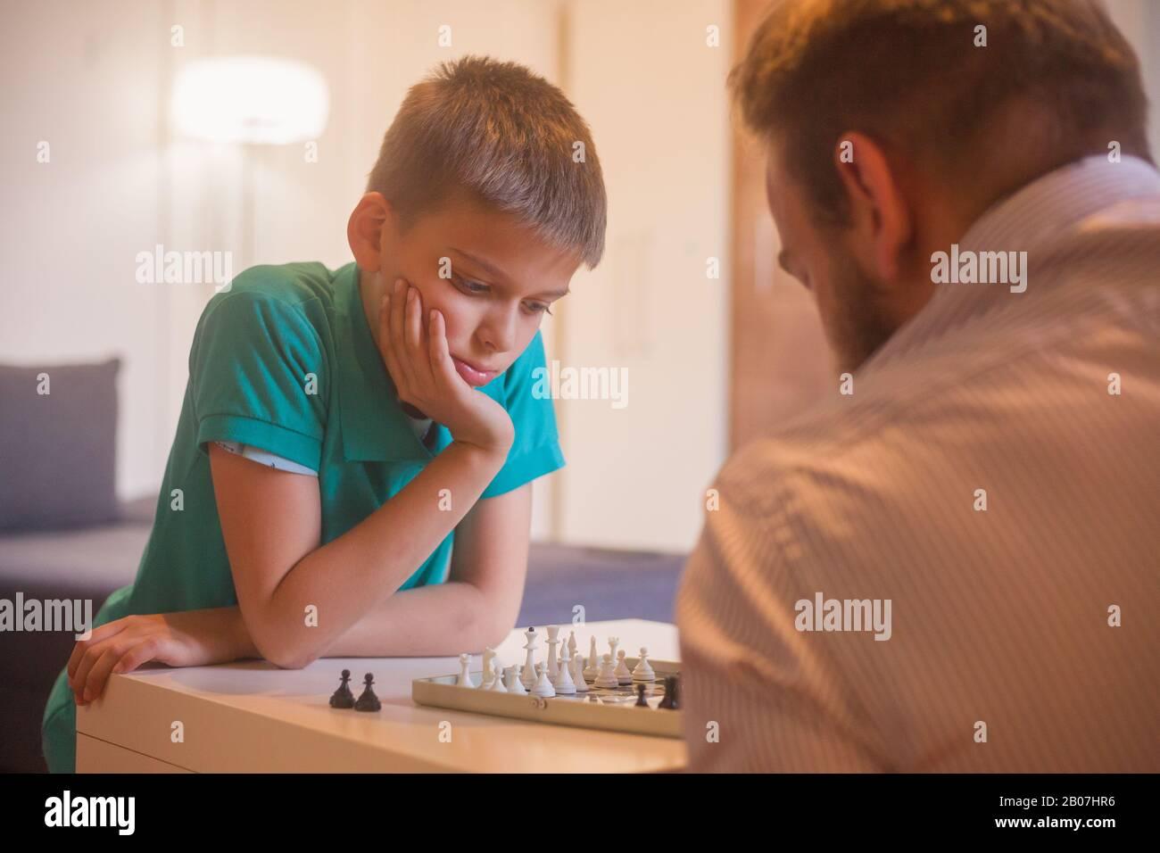 jeune homme et fils jouant aux échecs ensemble. Son fils s'accroche à son prochain mouvement. Banque D'Images