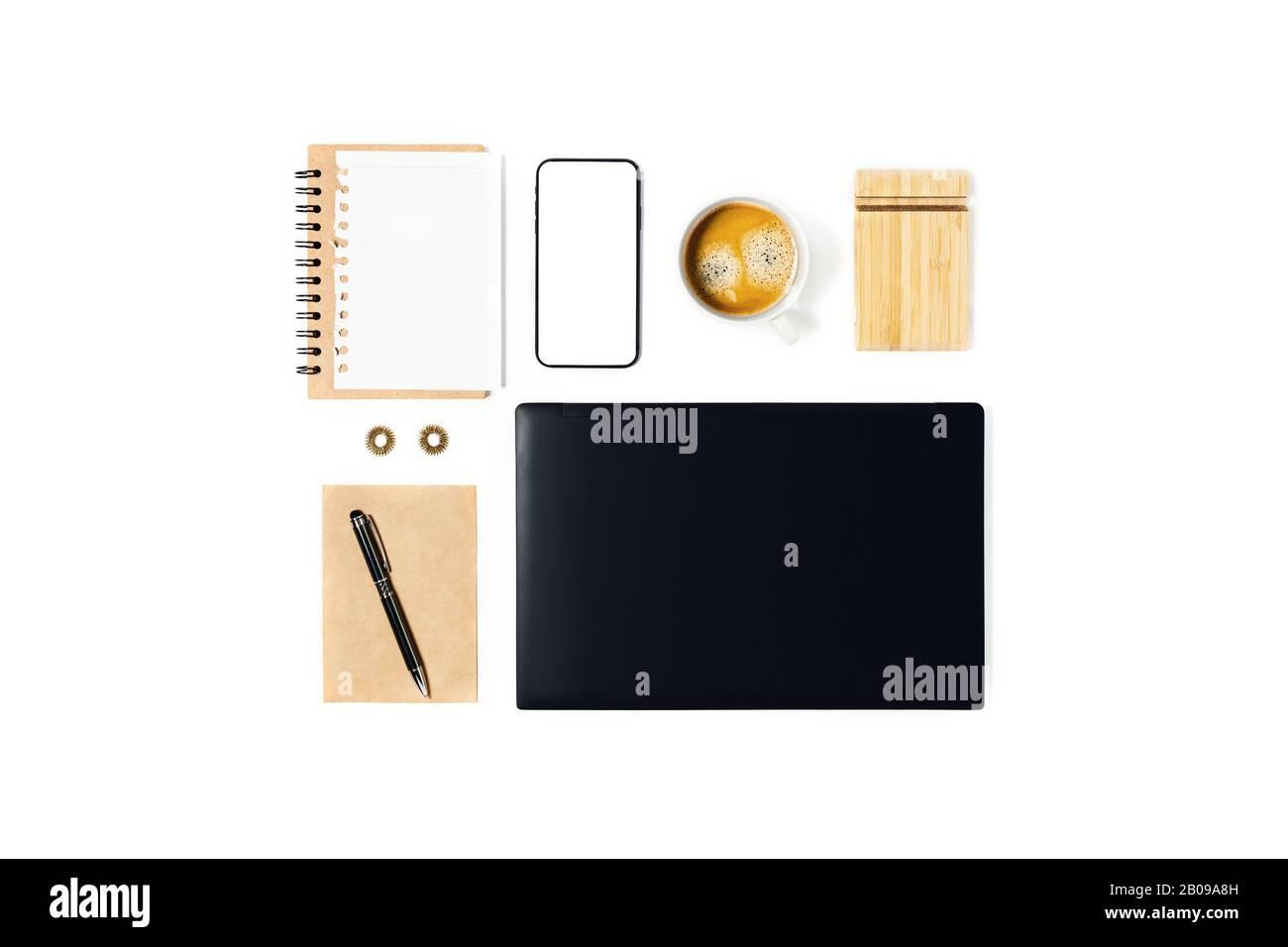 Espace de travail avec ordinateur portable, ordinateur portable, smartphone, cafetière et stylo, enveloppe sur fond blanc. Banque D'Images