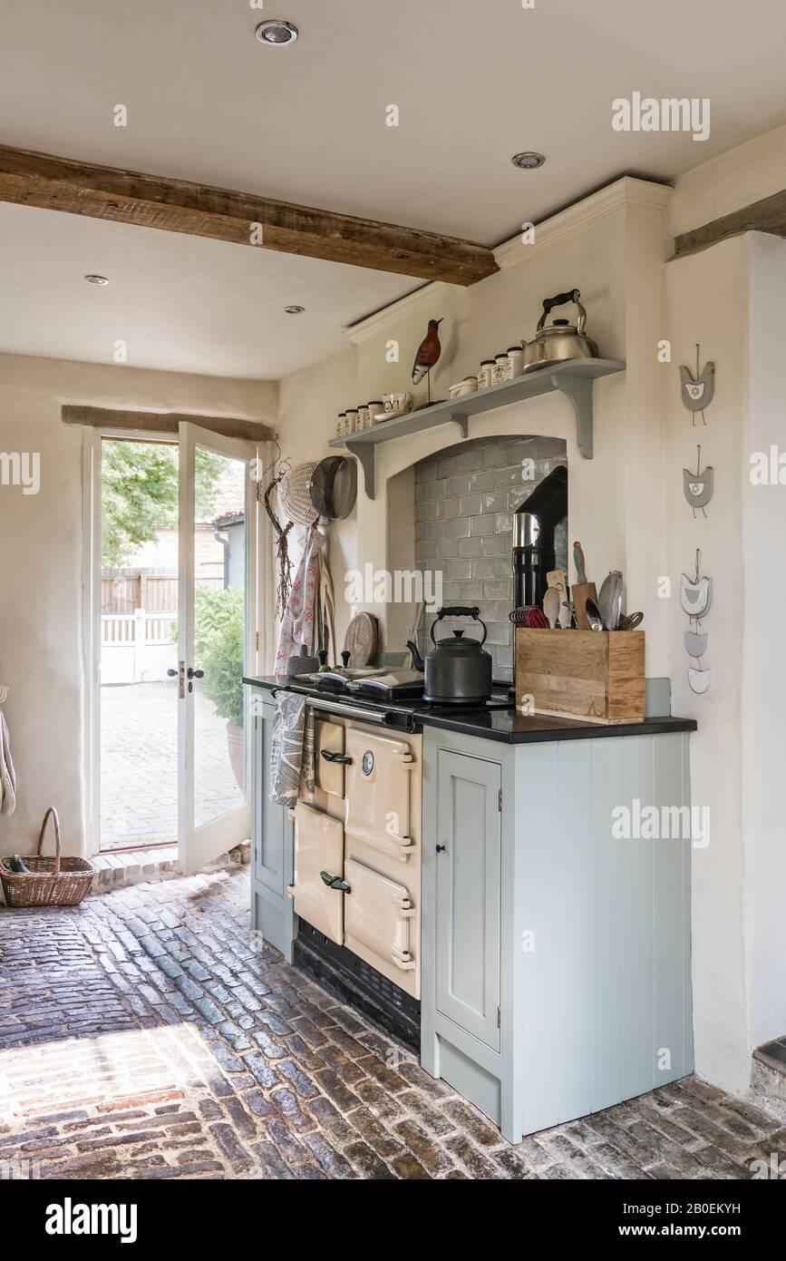 Cuisine équipée de bleu clair avec sol en pavés Rayburn dans la cuisine peinte à Farrow & ball's Matstick avec sol pavé d'origine. Banque D'Images