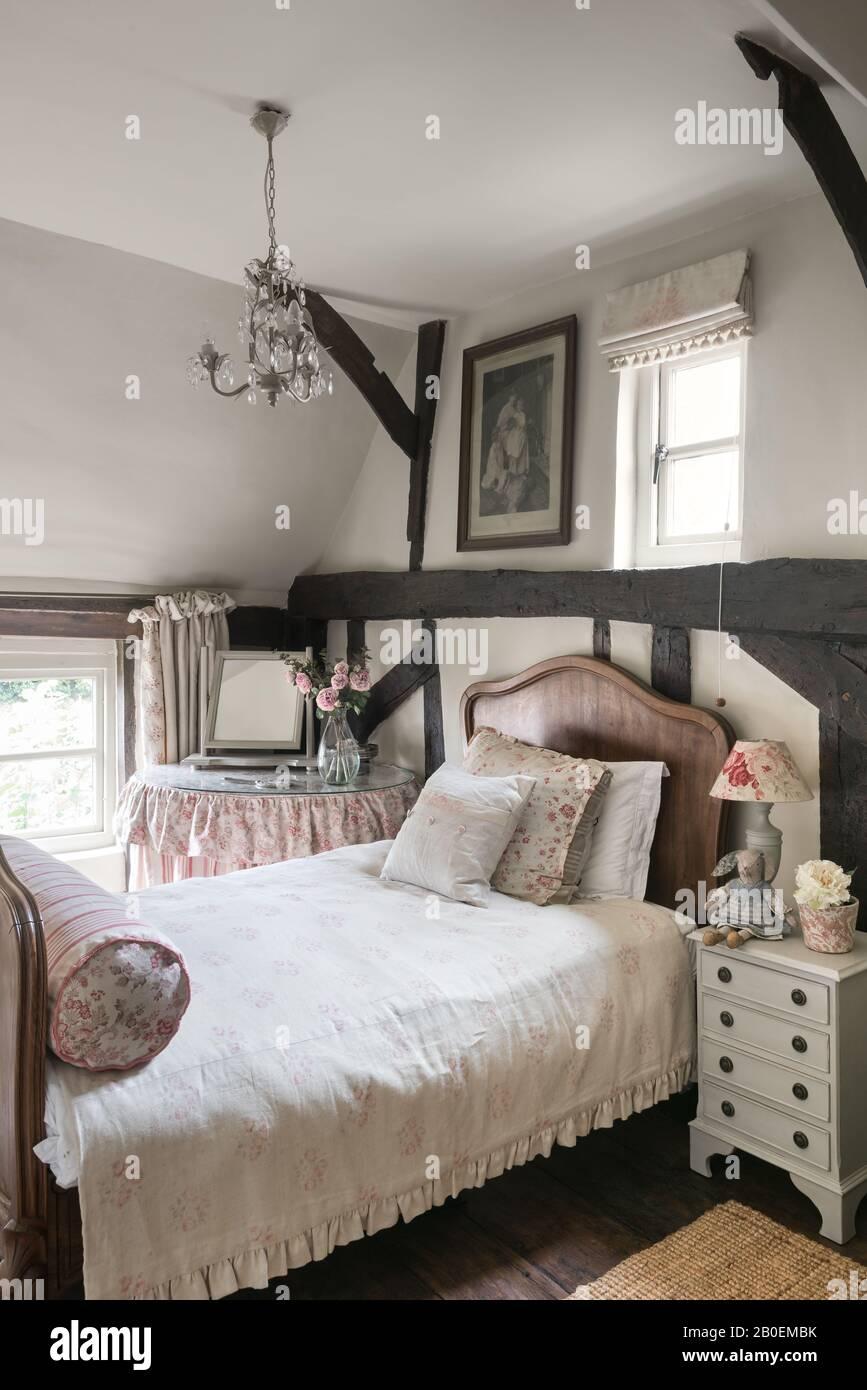 Tissus vintage dans la chambre avec lit français ancien et parquet et poutres en bois d'origine Banque D'Images