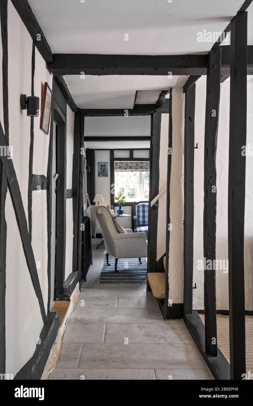 Passage à poutres apparentes entre la cuisine et le hall d'entrée avec sol en calcaire et chaise Napoléon française. Banque D'Images
