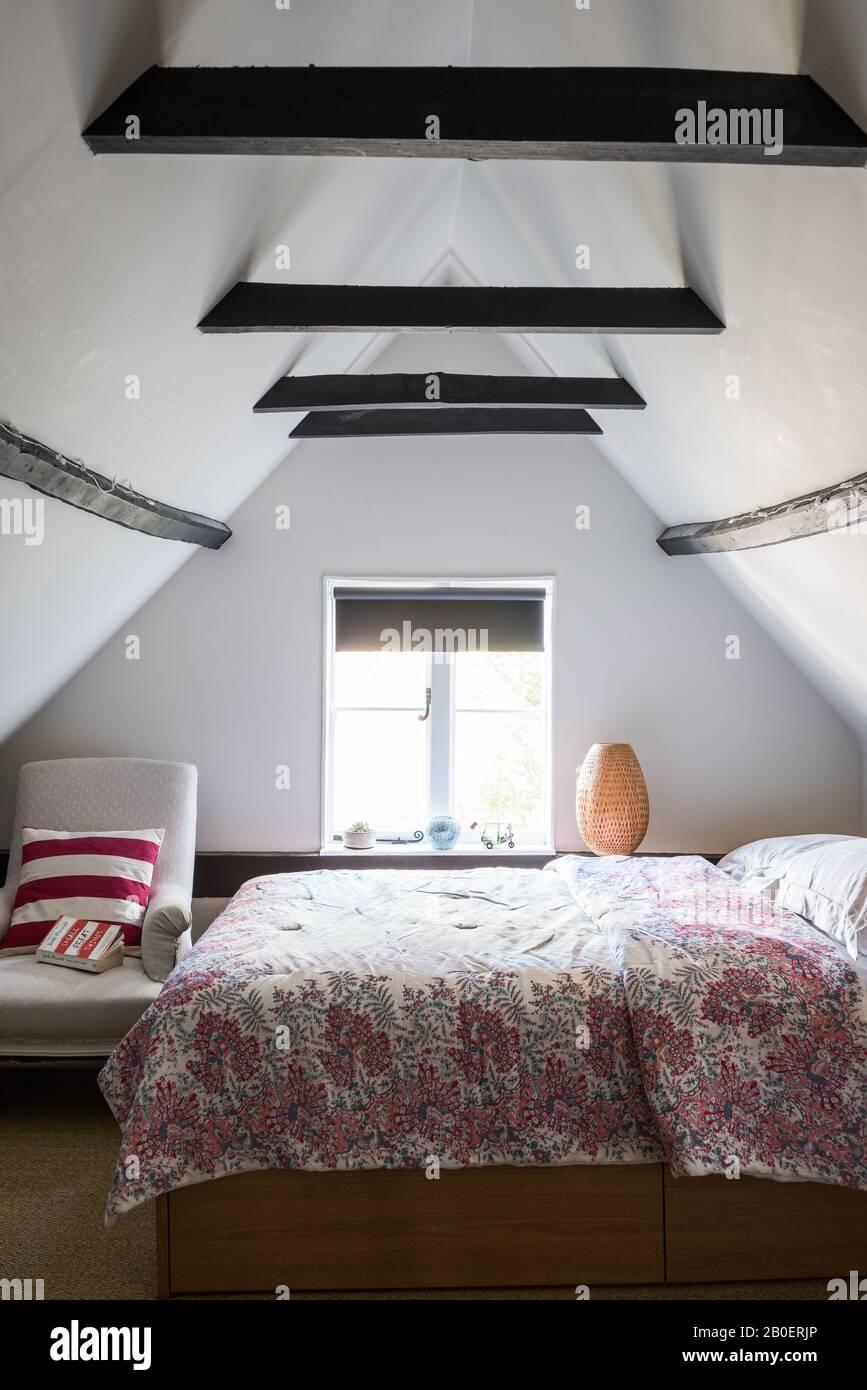 Chambre mansardée meublée simplement avec fauteuil couvert de lin français du XIXe siècle à côté du lit. Couette d'Oka. Banque D'Images
