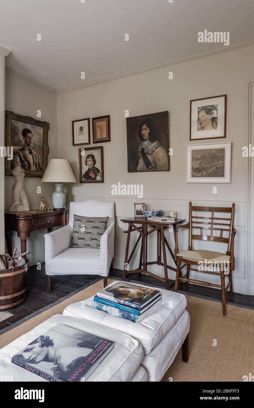 Fauteuil rembourré de Stephen Pardy avec tabourets pour plus de sièges et œuvres d'art encadrées. Banque D'Images