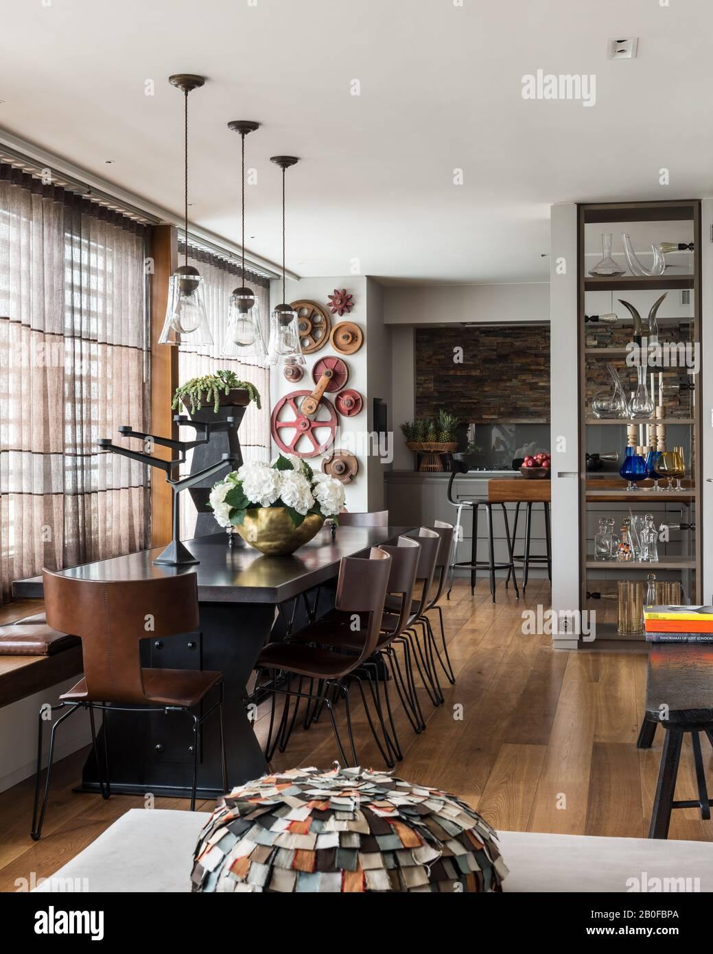 Luminaires suspendus en verre au-dessus de la table à manger De L'Arxe avec hydracea dans un vase en cuivre Banque D'Images