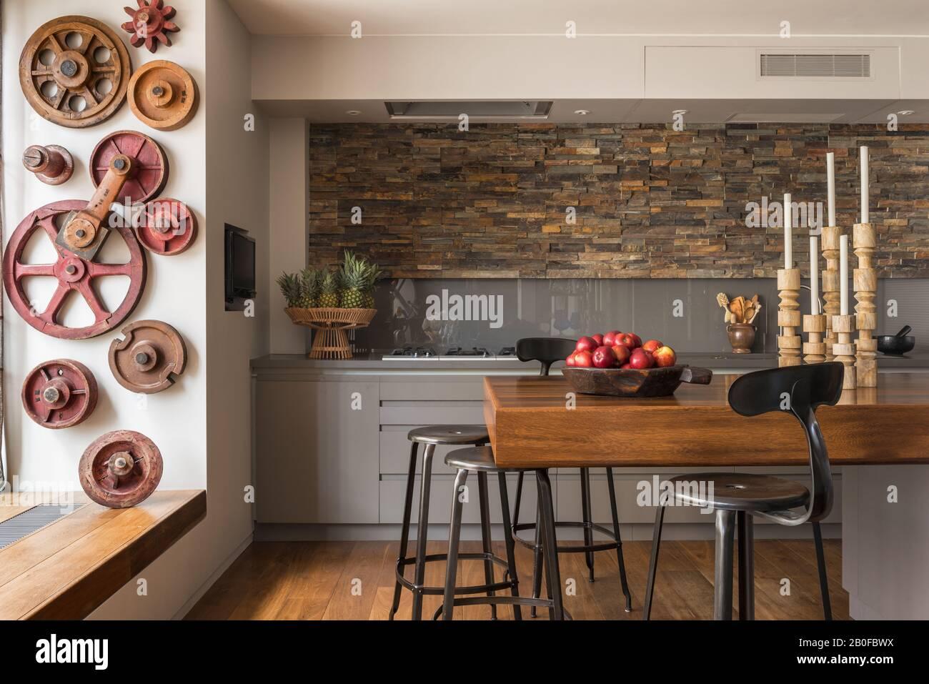 Bar à petit-déjeuner en teck avec murs ornés d'ardoise dans la cuisine de l'appartement moderne de West London. Banque D'Images