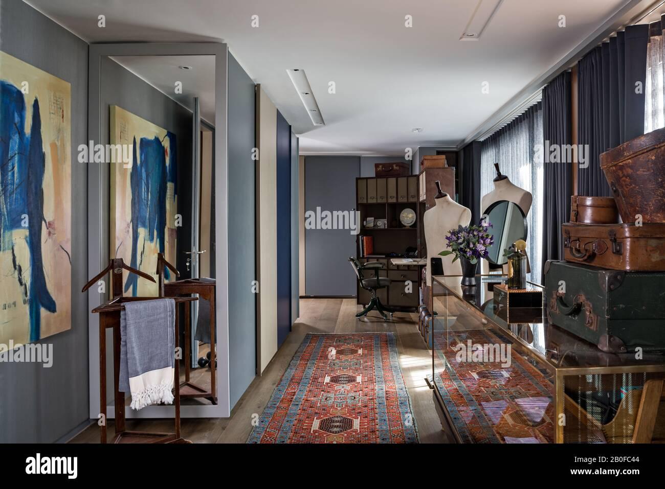 Valises anciennes sur l'armoire d'affichage avec presse à pantalons et mannequins mâles dans l'appartement moderne de West London. Banque D'Images