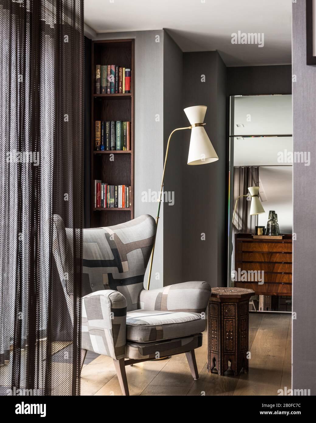 Lampe de plancher moderniste Diablo et fauteuil rembourré dans la chambre de l'appartement de West London Banque D'Images
